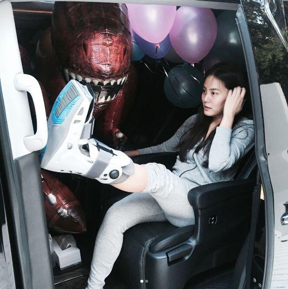 เจนี่ เทียนโพธิ์สุวรรณ ใส่เฝือก นั่งรออยู่บนรถขณะเอาลูกโป่งมาให้หลาน